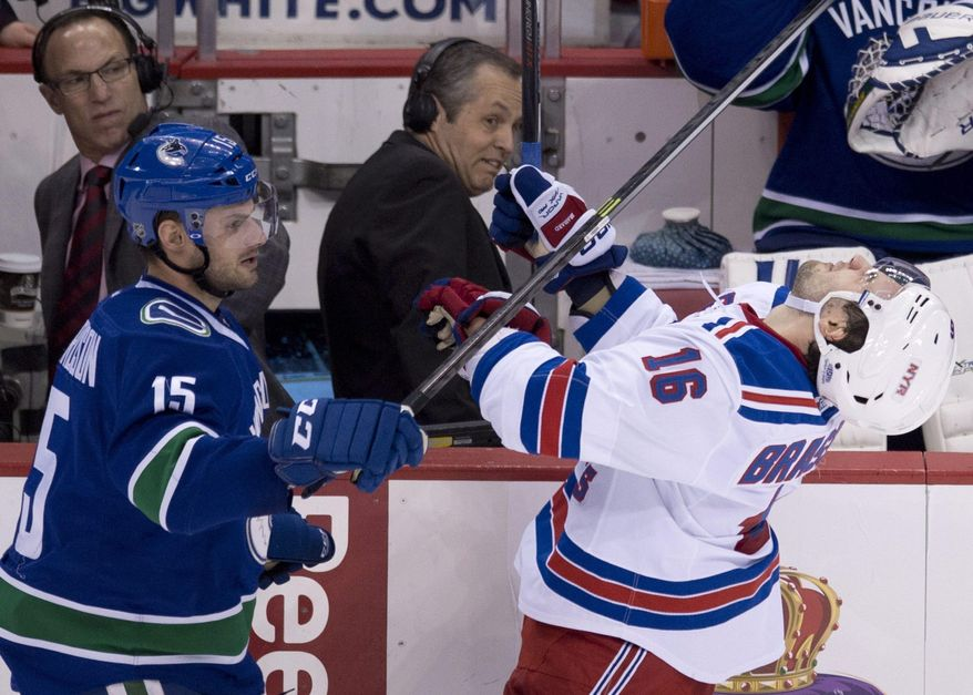 New York Rangers center Derick Brassard (16) gets a stick to the face from Vancouver Canucks center Brad Richardson (15) during the second period of an NHL hockey game Tuesday, April 1, 2014, in Vancouver, British Columbia. (AP Photo/The Canadian Press, Jonathan Hayward)