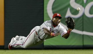 Philadelphia Phillies right fielder Marlon Byrd lays out for a fly out by Texas Rangers' Donnie Murphy in the sixth inning of a baseball game, Tuesday, April 1, 2014, in Arlington, Texas. Mitch Moreland was out at first trying to get back after heading to second on the play. The Rangers won 3-2. (AP Photo/Tony Gutierrez)