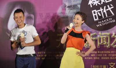 """In this Thursday, June 9, 2011 photo, actor Wen Zhang, left, and actress Yao Di attend a presser for their new TV series """"Naked Wedding""""  in Beijing, China. The Chinese actor's apology to his actress wife following rumors of his infidelity has set a record for comments and retweets on China's version of Twitter. (AP Photo) CHINA OUT"""