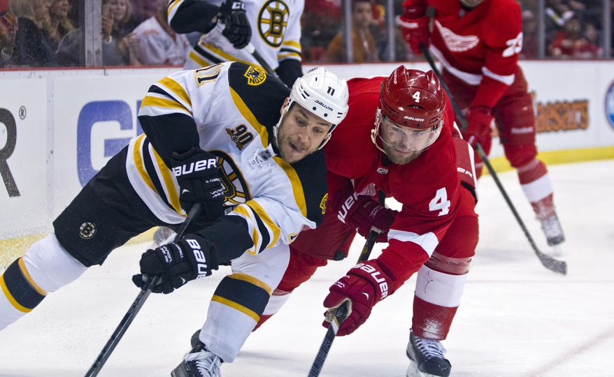 Boston Bruins forward Gregory Campbell, left, and defenseman Jakub Kindl (4), of the Czech Republic, contest for the puck against the boards during the first period of an NHL hockey game in Detroit, Mich., Wednesday, April 2, 2014. (AP Photo/Tony Ding)