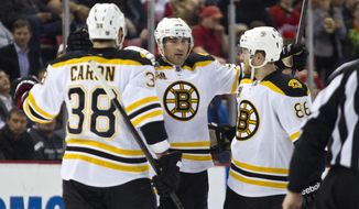 Boston Bruins defenseman Johnny Boychuk, center, celebrates his goal with forward Jordan Caron (38) and defenseman Kevan Miller, right, during the first period of an NHL hockey game against the Detroit Red Wings in Detroit, Mich., Wednesday, April 2, 2014. (AP Photo/Tony Ding)