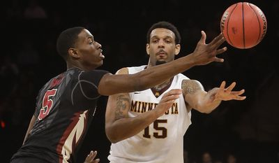 Minnesota's Maurice Walker (15) passes the ball away from Florida State's Jarquez Smith (5) during the first half of an NCAA college basketball game in the semifinals of the NIT on Tuesday, April 1, 2014, in New York. (AP Photo/Frank Franklin II)