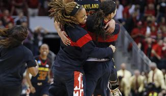 Maryland forward Alyssa Thomas, top,celebrates with guard Sequoia Austin, left, and another player after Maryland defeated Louisville 76-73 in a regional final of the NCAA women's college basketball tournament Tuesday, April 1, 2014, in Louisville, Ky. (AP Photo/John Bazemore)
