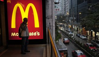 A man talks on a mobile phone next to a downtown McDonald's in Hong Kong, Wednesday, April 2, 2014. (AP Photo/Vincent Yu)
