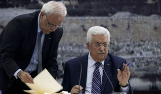 ** FILE ** In this Tuesday April 1, 2014 photo, Palestinian President Mahmoud Abbas, right, joined by Palestinian chief peace negotiator Saeb Erekat, signs an application to the U.N. agencies in the West Bank city of Ramallah. (AP Photo/Majdi Mohammed, File)
