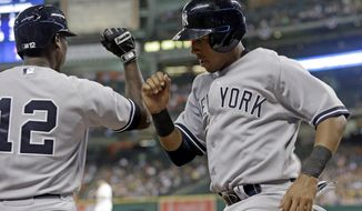 New York Yankees' Yangervis Solarte, right, knock arms with teammate Alfonso Soriano (12) after scoring from third base on a Carlos Beltran bases-loaded sacrifice fly against the Houston Astros in the third inning of a baseball game on Thursday, April 3, 2014, in Houston. (AP Photo/Pat Sullivan)
