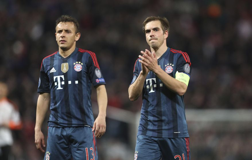 Bayern's Rafinha, left, and Philipp Lahm acknowledge the fans after the Champions League quarterfinal first leg soccer match between Manchester United and Bayern Munich at Old Trafford Stadium, Manchester, England, Tuesday, April 1, 2014.(AP Photo/Jon Super)