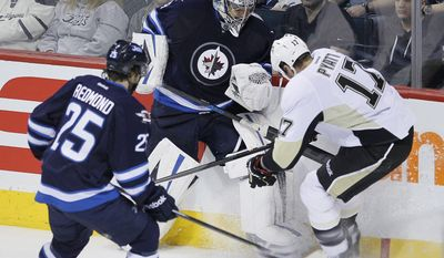 Winnipeg Jets goaltender Ondrej Pavelec (31) goes up against Pittsburgh Penguins' Taylor Pyatt (17) as Jets' Zach Redmond (25) watches during the third period of an NHL hockey game in Winnipeg, Manitoba, on Thursday, April 3, 2014. (AP Photo/The Canadian Press, John Woods)