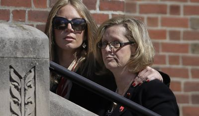 Kathy Crosby-Bell, right, mother of Boston firefighter Michael R. Kennedy, walks up the steps of Holy Name Church for her son's funeral in Boston, Thursday, April 3, 2014. Kennedy and Boston Fire Lt. Edward J. Walsh were killed Wednesday, March 26, 2014 when they were trapped in the basement of a burning brownstone during a nine-alarm blaze.(AP Photo/Stephan Savoia)