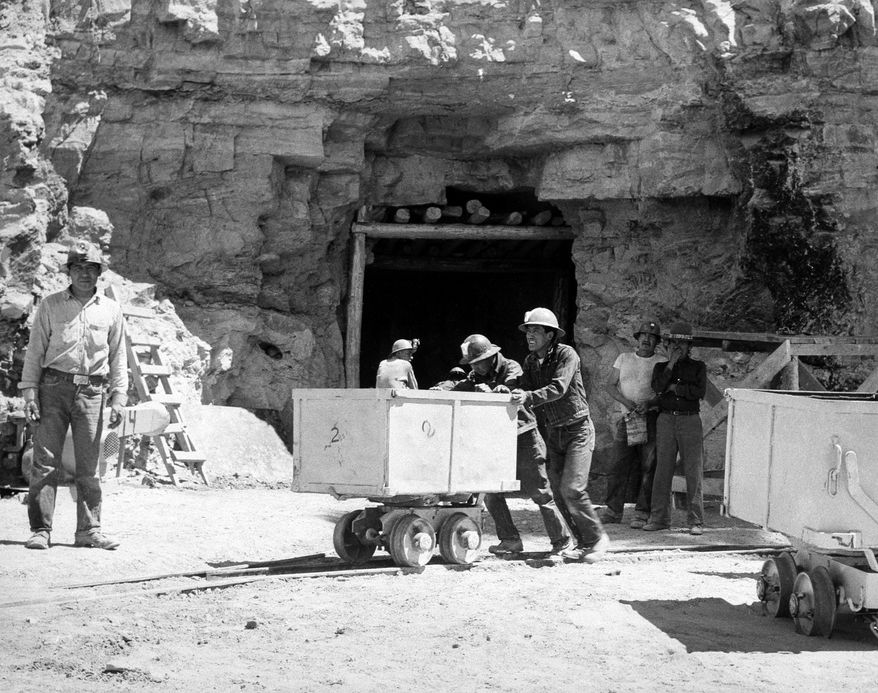 FILE - In this May 7, 1953, file photo, Navajo miners work at the Kerr McGee uranium mine at Cove, Ariz., on the Navajo reservation in Arizona. Kerr-McGee left abandoned uranium mine sites, including contaminated waste rock piles, in the Lukachukai mountains of Arizona and in the Ambrosia Lake area of New Mexico. The Lukachukai mountains are located immediately west of Cove, Ariz., and are a culturally significant part of the Navajo Nation. This site is among thousands that are part of the $5.15 billion settlement with Anadarko Petroleum Corp. with approximate amount of funding for cleanup efforts and details about the sites, in information provided by the Justice Department.  (AP Photo)