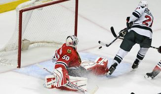 Minnesota Wild's center Kyle Brodziak (21) is blocked by Chicago Blackhawks goalie Corey Crawford (50) in the second period of an NHL hockey game in Chicago, Thursday, April 3, 2014. (AP Photo/David Banks)