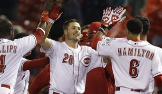 Cincinnati Reds' Chris Heisey (28) is congratulated by Brandon Phillips (4) and Billy Hamilton (6) after Heisey hit a bases-loaded single off St. Louis Cardinals relief pitcher Carlos Martinez to drive in the winning run in the bottom of the ninth inning of a baseball game, early Thursday, April 3, 2014, in Cincinnati. Cincinnati won 1-0. (AP Photo/Al Behrman)