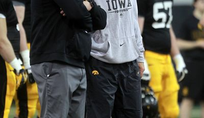 Iowa head coach Kirk Ferentz, front right, talks to his son and offensive line coach Brian Ferentz during NCAA college football practice on Wednesday, April 2, 2014, in Iowa City. (AP Photo/Iowa City Press-Citizen, David Scrivner) NO SALES