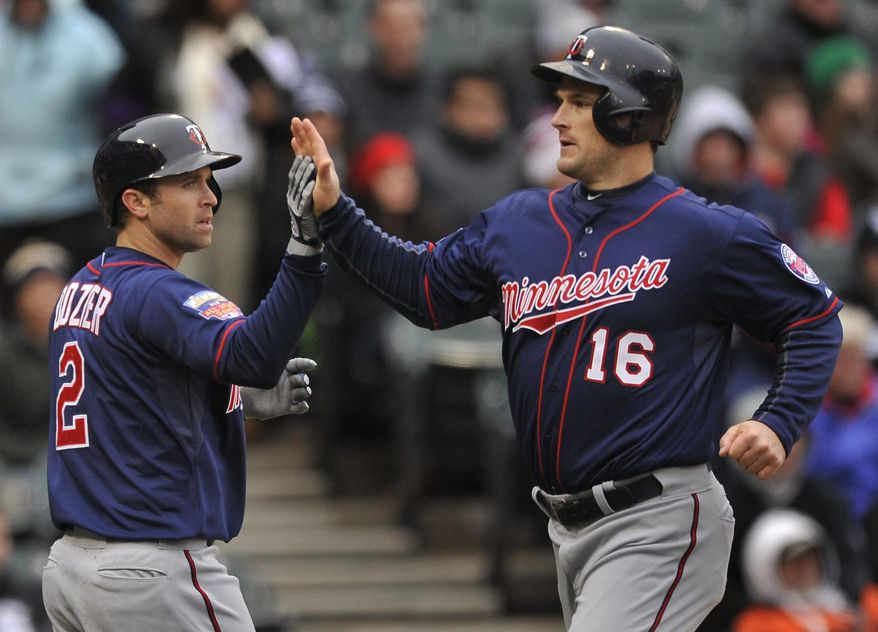 Minnesota Twins' Josh Willingham (16), and Brian Dozier (2), celebrate at home plate after both scoring on a 3-RBI double hit by Chris Colabello during the third inning of an baseball game against the Chicago White Sox in Chicago, Thursday, April 3, 2014. (AP Photo/Paul Beaty)
