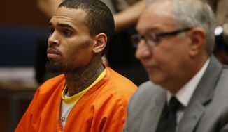 FILE In this Monday, March 17, 2014 file photo, R&B singer Chris Brown, left, appears at a hearing in Los Angeles Superior Court with his attorney Mark Geragos, for his probation violation after his arrest on March 14, in Los Angeles. The U.S. Marshals Service took Brown into custody from a Los Angeles jail on Wednesday, April 2, 2014, to transport him to Washington, D.C. for his upcoming trial on a misdemeanor assault charge. (AP Photo/Lucy Nicholson, Pool, file)