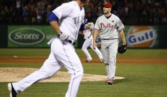 Philadelphia Phillies relief pitcher Jonathan Papelbon, right, leaves the field after walking in Texas Rangers' Jim Adduci, left, during the ninth inning of a baseball game on Wednesday, April 2, 2014, in Arlington, Texas. The Rangers won 4-3. (AP Photo/Jim Cowsert)