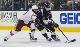 Los Angeles Kings defenseman Drew Doughty (8) and Phoenix Coyotes forward Brandon Mcmillan (38) vie for the puck during the first period of an NHL hockey game, Wednesday, April 2, 2014, in Los Angeles.  (AP Photo/Ringo H.W. Chiu)