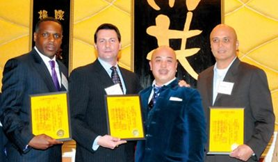 """FILE - In this file photo taken March 16, 2011, Raymond """"Shrimp Boy"""" Chow, second from right, poses with several inducted consultants, including Keith Jackson, left, a former San Francisco school board member, at the Chee Kung Tong spring banquet in San Francisco. Jackson, who is playing a key role in the cash-for-guns political corruption investigation that has ensnared California state Sen. Leland Yee, appeared in federal court Thursday, April 3, 2014 for a bail hearing on charges that include bribery, drugs, guns and murder-for-hire conspiracy. Jackson was ordered released from jail pending trial. (AP Photo/Sing Tao Daily, File)"""