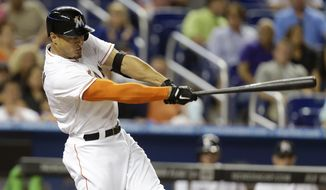 Miami Marlins' Giancarlo Stanton hits a two-run home run in the sixth inning of a baseball game against the Colorado Rockies, Wednesday, April 2, 2014, in Miami. The Rockies defeated the Marlins 6-5. (AP Photo/Lynne Sladky)