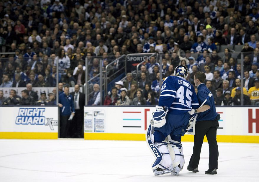 Toronto Maple Leafs goaltender Jonathan Bernier is helped off the ice after being injured during the third period of an NHL hockey game against the Boston Bruins in Toronto on Thursday, April 3, 2014. (AP Photo/The Canadian Press, Frank Gunn)