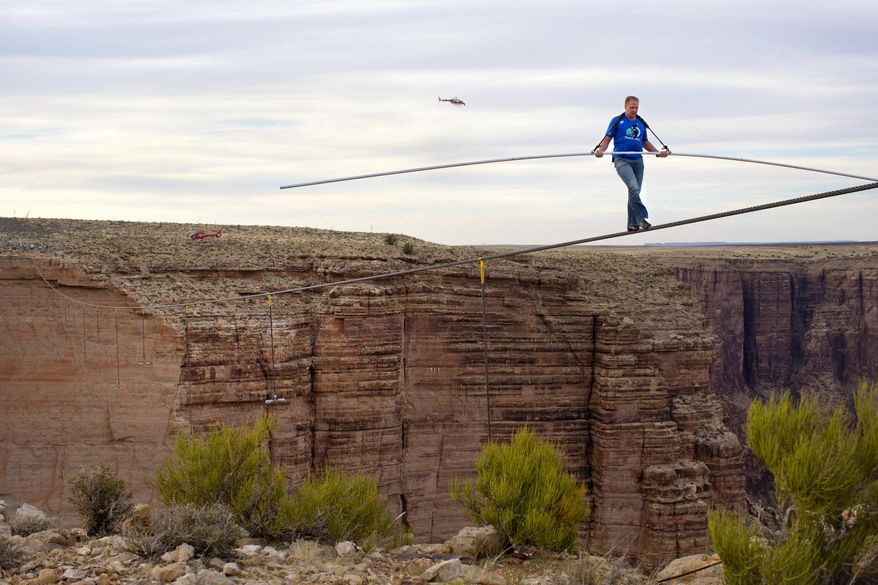 """FILE - This June 23, 2013 file photo released by Discovery shows Nik Wallenda walking across the Little Colorado River Gorge on the Navajo Nation near Cameron, Ariz., for Discovery Channel's """"Skywire Live With Nik Wallenda."""" Wallenda is taking his tightrope to Chicago for a high-wire walk to be televised this fall on Discovery, part of the network's strategy to entice viewers with live events. Wallenda's walk across the Grand Canyon last year reached more than 10 million viewers live on Discovery. His encore will probably take place in November, Discovery said on Thursday, April 3, 2014. (AP Photo/Discovery, Tiffany Brown, File)"""