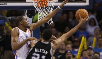 Oklahoma City Thunder forward Kevin Durant (35) attempts to block a shot by San Antonio Spurs forward Tim Duncan (21) in the second quarter of an NBA basketball game in Oklahoma City, Thursday, April 3, 2014. (AP Photo/Sue Ogrocki)