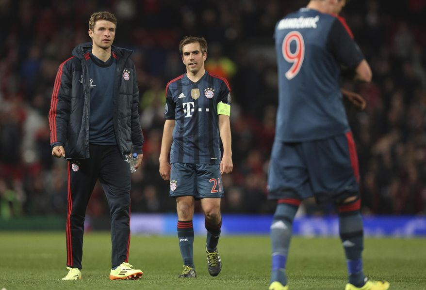Bayern's Thomas Mueller, Philipp Lahm and  Mario Mandzukic, from left, leave the pitch after the Champions League quarterfinal first leg soccer match between Manchester United and Bayern Munich at Old Trafford Stadium, Manchester, England, Tuesday, April 1, 2014.(AP Photo/Jon Super)