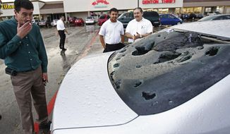 Pablo Loza, left, looks at damage to his car which took a beating during a hailstorm while parked in a lot outside a thrift store, Thursday, April 3, 2014, in Denton, Texas. Severe thunderstorms in North Texas on Thursday spawned a reported tornado in one town and pummeled Denton with hail as large as softballs. (AP Photo/The Dallas Morning News, Nathan Hunsinger) MANDATORY CREDIT; MAGS OUT; TV OUT; INTERNET USE BY AP MEMBERS ONLY; NO SALES