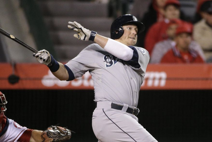 Seattle Mariners' Justin Smoak follows through on a home run during the ninth inning of a baseball game against the Los Angeles Angels on Wednesday, April 2, 2014, in Anaheim, Calif. (AP Photo/Jae C. Hong)