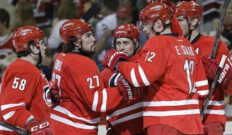 Carolina Hurricanes' Chris Terry (58), Justin Faulk (27), John-Michael Liles (26), Eric Staal (12) and Jordan Staal, back right, celebrate Liles' goal against the Dallas Stars during the second period of an NHL hockey game in Raleigh, N.C., Thursday, April 3, 2014. (AP Photo/Gerry Broome)