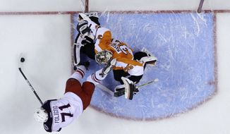 Columbus Blue Jackets' Nick Foligno, left, tries to get a shot past Philadelphia Flyers goalie Steve Mason during the first period of an NHL hockey game, Thursday, April 3, 2014, in Philadelphia. (AP Photo/Matt Slocum)