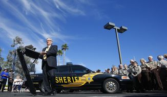 With a volunteer posse looking on, Maricopa County Sheriff Joe Arpaio talks about three Maricopa County sheriff's volunteer posses that had temporarily suspended operations are back at work after officials say they have resolved a question over who will provide insurance coverage for posse-owned vehicles, at a news conference, Thursday, April 3, 2014, in Sun City, Ariz. (AP Photo/Ross D. Franklin)