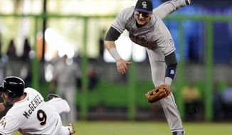 Colorado Rockies shortstop Troy Tulowitzki, right, watches his throw to first base after forcing out Miami Marlins' Casey McGehee (9) out at second base during the first inning of a baseball game, Thursday, April 3, 2014, in Miami. The Marlins' Garrett Jones was out a first for a double play. (AP Photo/Lynne Sladky)