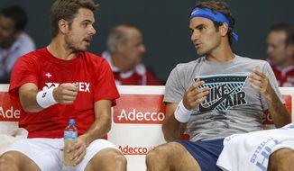 Stanislas Wawrinka, left, of Switzerland, and Roger Federer, right, of Switzerland, speak together during a training session of the Swiss Davis Cup tennis team prior to the Davis Cup World Group quarterfinal match between Switzerland and Kazakhstan, , in Geneva, Switzerland, Wednesday, April 2, 2014. The Davis Cup World Group quarterfinal between Switzerland and  Kazakhstan will take place from April  4 to April 6. (AP Photo/Keystone,Salvatore Di Nolfi)