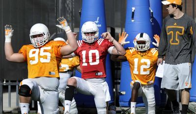 In this March 11, 2014 photo, Tennessee defensive lineman Danny O'Brien, left, quarterback Riley Ferguson, and defensive back Emmanuel Moseley take part in a stretching exercise during an NCAA college spring football practice in Knoxville, Tenn. (AP Photo/The Knoxville News Sentinel, Adam Lau)