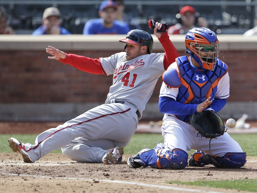 Washington Nationals' Sandy Leon, left, slides safely home past New York Mets catcher Travis d'Arnaud during the fifth inning of a baseball game at Citi Field, Thursday, April 3, 2014 in New York. (AP Photo/Seth Wenig)