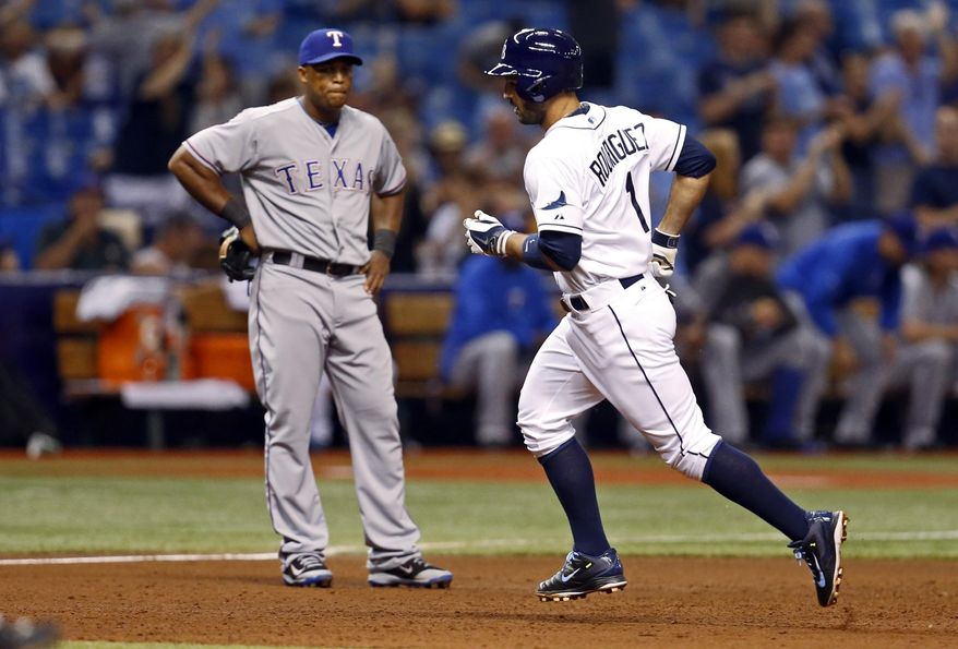 Tampa Bay Rays' Sean Rodriguez rounds the bases in front of Texas Rangers third baseman Adrian Beltre after hitting a three-run home run during the third inning of a baseball game Friday, April 4, 2014, in St. Petersburg, Fla. (AP Photo/Mike Carlson)