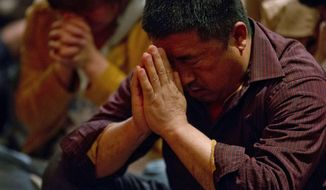 Relatives of Chinese passengers onboard the Malaysia Airlines plane, MH370 pray in a prayer room in Beijing, China, Friday, April 4, 2014. An arduous weeks-long hunt has not turned up a single piece of wreckage, which could have led the searchers to the plane and eventually to its black boxes containing key information about the flight. But the searchers have apparently decided to make a direct attempt to find the devices, whose batteries last about a month. (AP Photo/Ng Han Guan)