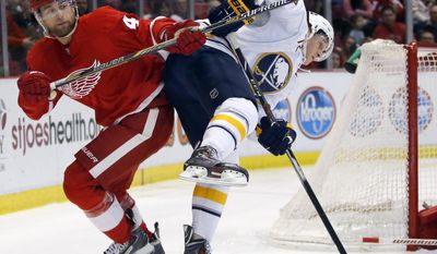 Detroit Red Wings' Jakub Kindl (4), of the Czech Republic, knocks Buffalo Sabres' Luke Adam (72) off-balance during the first period of an NHL hockey game Friday, April 4, 2014, in Detroit. (AP Photo/Duane Burleson)