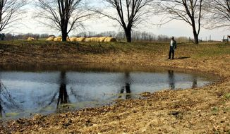 FILE - In this April 2, 2002, file photo, dairy farmer Paul Peter stands by his emergency pond near his house at Castleton-on-Hudson, N.Y. Industry groups and more than a dozen GOP senators are urging the Obama administration to reconsider a proposal by the EPA and the Army Corps of Engineers. The new rule seeks to clarify which waters or wetlands would trigger federal requirements, such as permitting and state water quality certification. Seasonal and rain-dependent streams, and wetlands near rivers and streams, would be covered; others would be considered on a case-by-case basis to determine if they play a significant role in the quality of downstream waters. Landowners and developers say the government has gone too far in regulating isolated ponds or marshes with no direct connection to navigable waterways. (AP Photo/Jim McKnight, File)