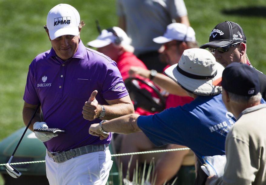 Phil Mickelson gives a thumbs-up to fans as he walks to the ninth hole during the second round of the Houston Open golf tournament, on Friday, April 4, 2014, in Humble, Texas. (AP Photo/Patric Schneider)
