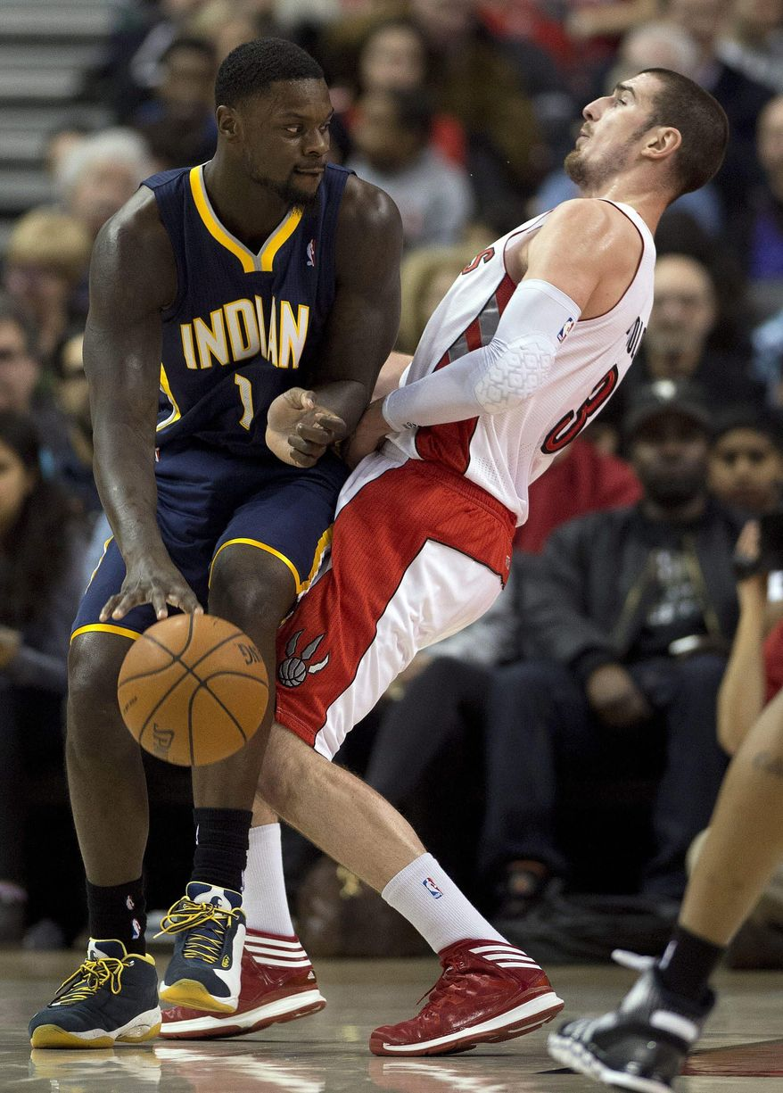 Toronto Raptors guard Nando De Colo, right, is fouled by Indiana Pacers guard Lance Stephenson during the first half of an NBA basketball game Friday, April 4, 2014, in Toronto. (AP Photo/The Canadian Press, Frank Gunn)