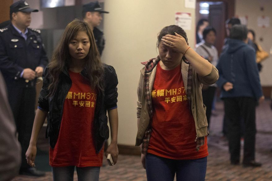 "Relatives of the Chinese passengers onboard the Malaysia Airlines flight MH370 wear T-shirts with the words ""Pray for MH370, safe return"" in Beijing Thursday, April 3, 2014. No trace of the Boeing 777 has been found nearly a month after it vanished in the early hours of March 8 on a flight from Kuala Lumpur to Beijing with 239 people on board. (AP Photo/Ng Han Guan)"