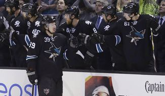 San Jose Sharks center Logan Couture (39) is congratulated by teammates after scoring during the second period of an NHL hockey game against the Los Angeles Kings in San Jose, Calif., Thursday, April 3, 2014. (AP Photo/Jeff Chiu)