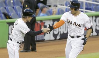 Miami Marlins' Giancarlo Stanton, right, is congratulated by third base coach Brett Butler as he rounds third base during the first inning of a baseball game against the San Diego Padres, Friday, April 4, 2014, in Miami. (AP Photo/Wilfredo Lee)