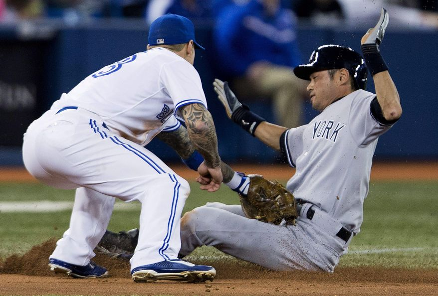Toronto Blue Jays third baseman Brett Lawrie, left, tags out New York Yankees right fielder Ichiro Suzuki at third base during fifth inning AL baseball action in Toronto on Friday, April 4, 2014. (AP Photo/The Canadian Press,Peter Power)