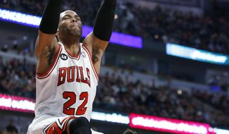 Chicago Bulls forward Taj Gibson, left, scores in front of Milwaukee Bucks guard Jeff Adrien during the first half of an NBA basketball game in Chicago, Friday, April 4, 2014. (AP Photo/Kamil Krzaczynski)