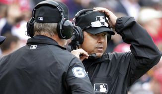 Umpires Jim Joyce, left, and Doug Eddings talk on head phones as they review a call during the fifth inning of a baseball home opener between the Washington Nationals and Atlanta Braves at Nationals Park Friday, April 4, 2014, in Washington. Ian Desmond's inside-the-park homer was overturned on replay review and changed to a ground-rule double.(AP Photo/Alex Brandon)