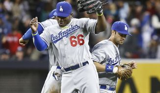 Los Angeles Dodgers' Yasiel Puig, center, Andre Ethier, right, and Carl Crawford do their bump celebration after the Dodgers' 3-2 victory over the San Diego Padres in a baseball game Tuesday, April 1, 2014, in San Diego.  (AP Photo/Lenny Ignelzi)