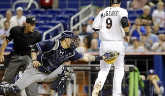 San Diego Padres catcher Yasmani Grandal, center, is unable to tag Miami Marlins' Casey McGehee (9) who scores on a double by Garrett Jones during the fifth inning of a baseball game on Friday, April 4, 2014, in Miami. (AP Photo/Wilfredo Lee)